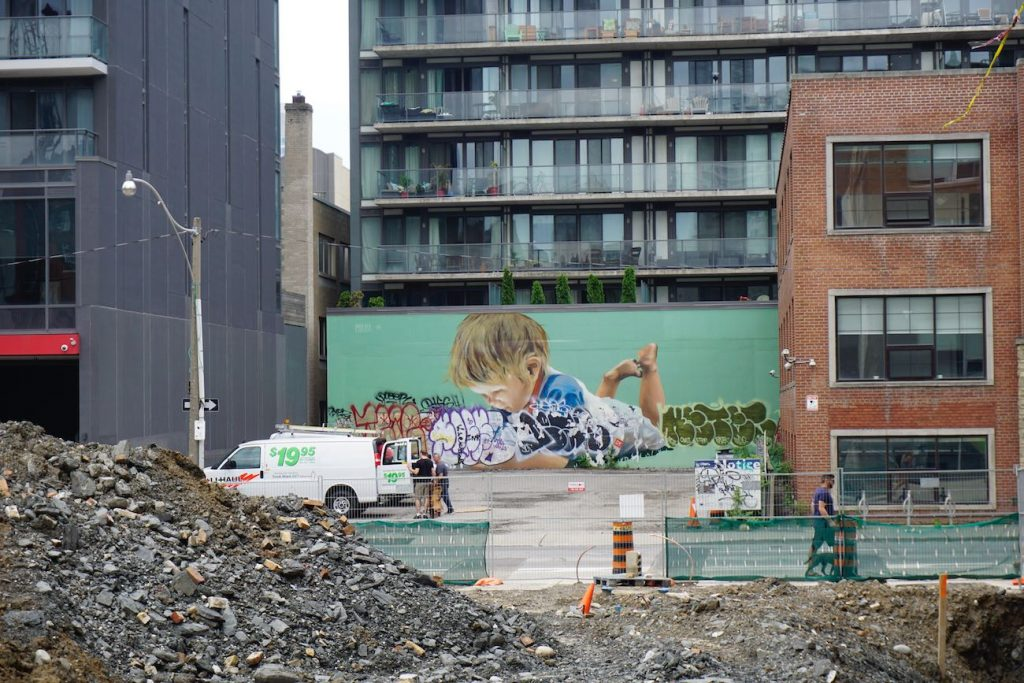 a huge mural of a toddler playing while lying on their stomach
