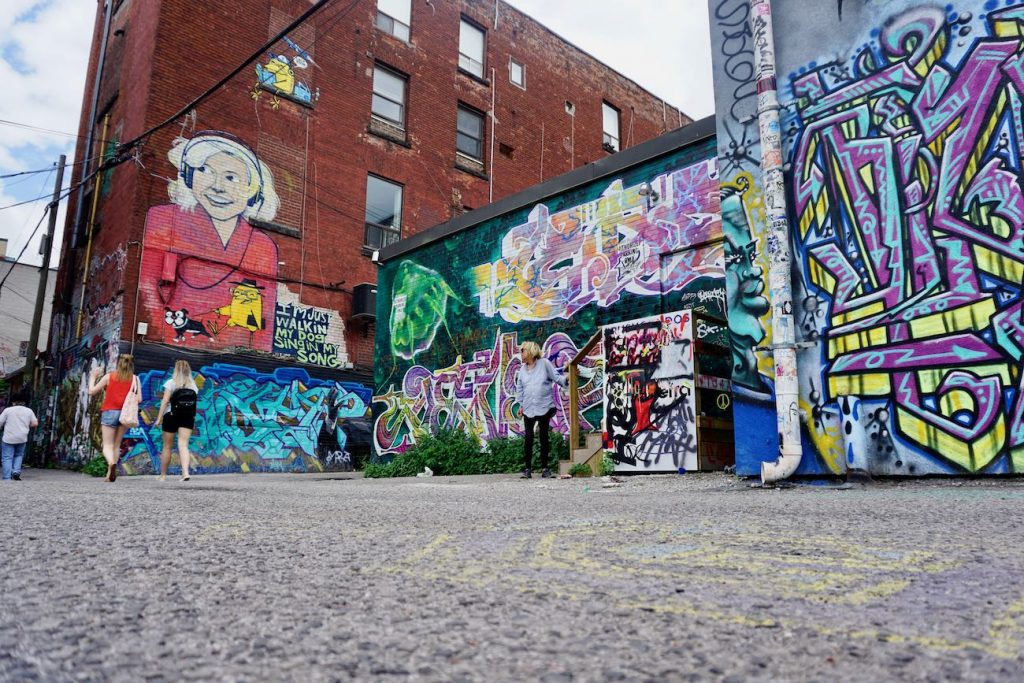A low angle shot of graffiti alley with tourists walking by